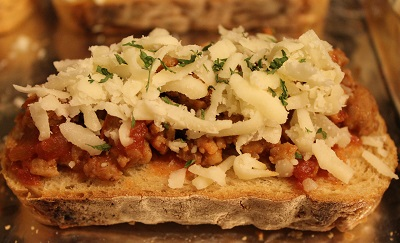 Italian Sausage Bruschetta ready to broil | Italian sausage bruschetta looks and tastes sophisticated, but is very easy to make. Serve it at a party or use it to make an everyday dinner feel special.